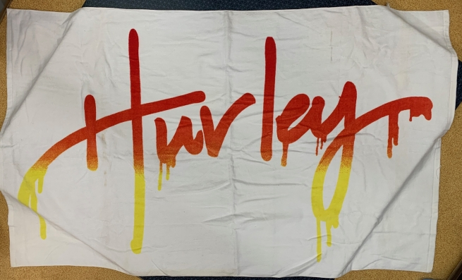 Белое полотенце с красно-желтой крупной надписью