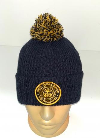Черная шапка с желтой нашивкой и помпоном