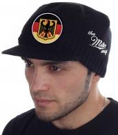 Вязаная кепка для парней и мужчин. Недорогая брендовая модель Miller Way с козырьком и гербом Германии на фоне флага Федеративной Республики. Без попсового декора