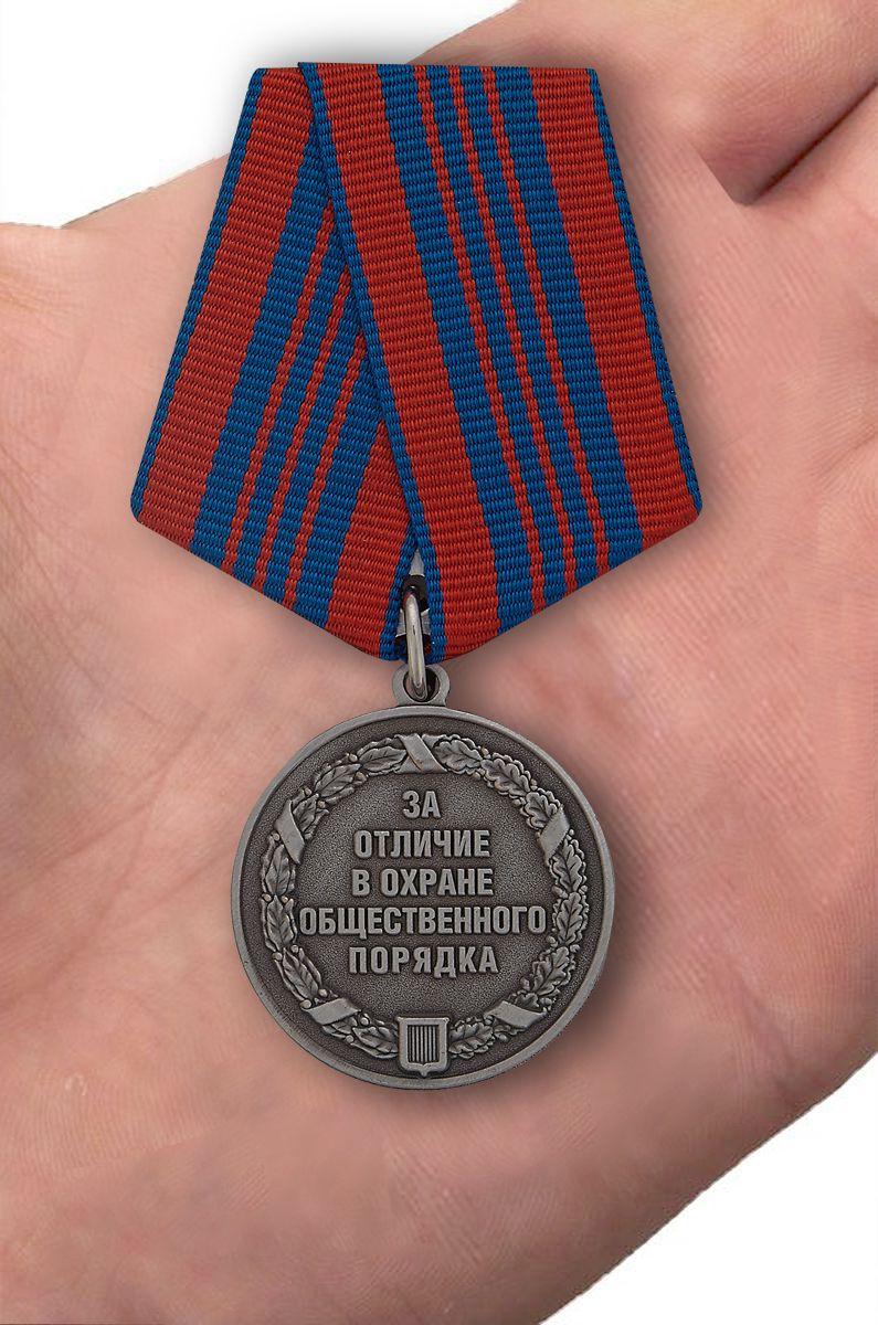 """Латунная медаль """"За отличие в охране общественного порядка"""" в красивом футляре из флока с пластиковой крышкой - вид на ладони"""