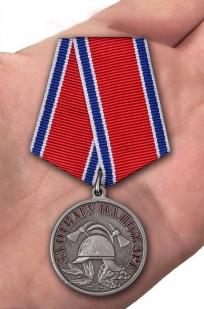 "Латунная медаль МЧС ""За отвагу на пожаре"" - вид на ладони"