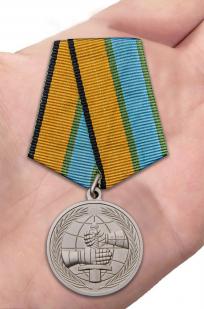 Латунная медаль МО РФ За вклад в развитие международного военного сотрудничества - вид на ладони