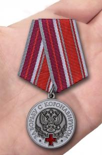 Латунная медаль За борьбу с коронавирусом - вид на ладони