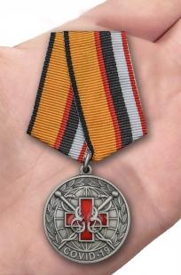 Латунная медаль За борьбу с пандемией COVID-19 - вид на ладони