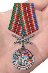 Латунная медаль За службу в Камчатском пограничном отряде - вид на ладони