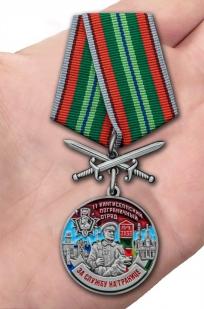Латунная медаль За службу в Кингисеппском пограничном отряде - вид на ладони