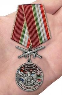 Латунная медаль За службу в Московском пограничном отряде - вид на ладони