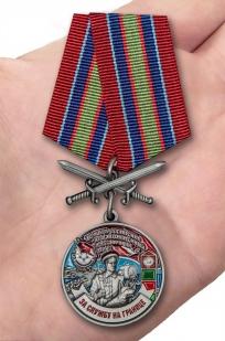 Латунная медаль За службу в Новороссийском пограничном отряде - вид на ладони