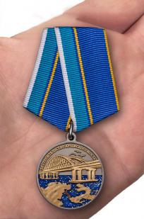"""Латунная медаль """"За строительство Крымского моста"""" - вид на ладони"""