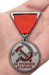 Латунная медаль За трудовое отличие СССР - вид на ладони