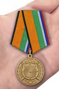 Латунная медаль За вклад в укрепление обороны РФ - вид на ладони