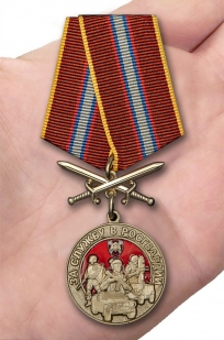Латунная медаль За службу в Росгвардии - вид на ладони