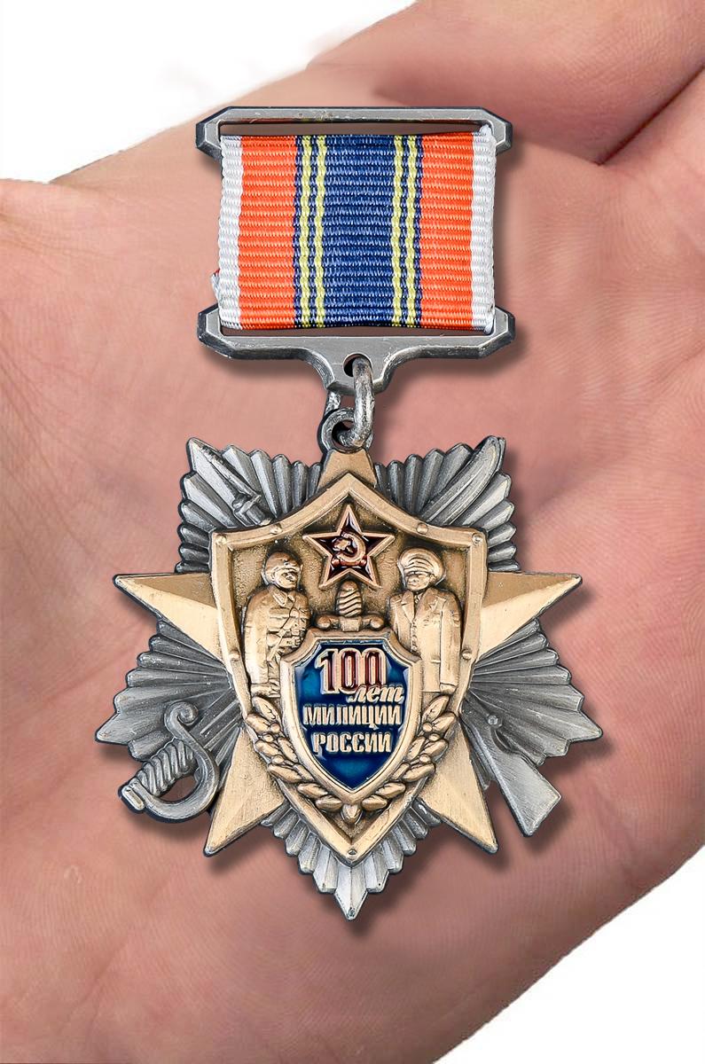 Латунный знак 100 лет милиции России - вид на ладони