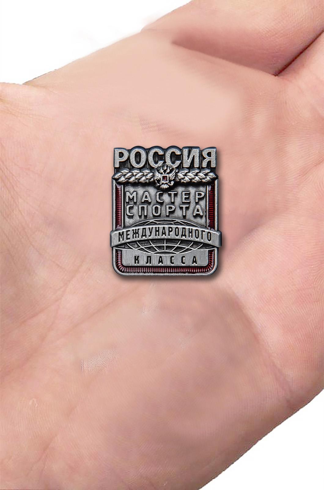 Латунный знак Мастер спорта России Международного класса - вид на ладони