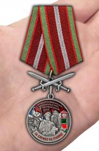 Латунная медаль За службу в Забайкальском пограничном округе - вид на ладони