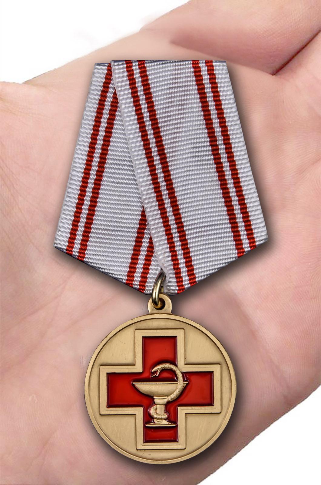 Латунная медаль За заслуги в медицине - вид на ладони