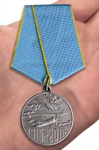 """Медаль """"100 лет Истребительной авиации"""" в футляре из бархатистого флока - вид на ладони"""