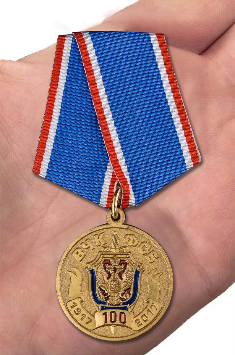 Медаль 100 лет ВЧК-ФСБ в футляре из бордового флока - вид на ладони