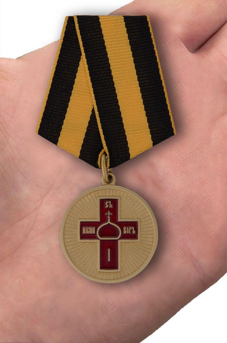 """Медаль """"Дело веры"""" в футляре из флока бордового цвета - вид на ладони"""
