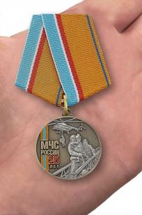 """Медаль """"МЧС России 25 лет"""" в футляре из флока темно-бордового цвета - вид на ладони"""