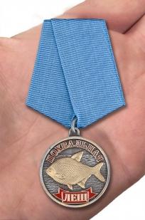 """Медаль рыбака """"Лещ"""" в наградном футляре с покрытием из флока - вид на ладони"""