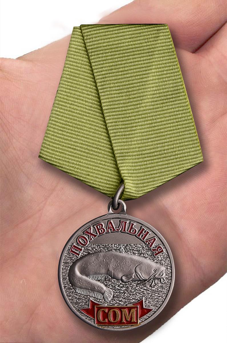 """Медаль рыбака """"Сом"""" в футляре из флока бордового цвета – вид на ладони"""