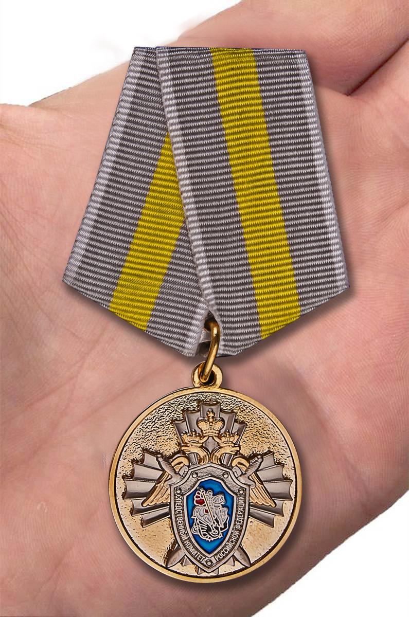 """Медаль СК РФ """"За заслуги"""" в красивом футляре с покрытием из флока - вид на ладони"""