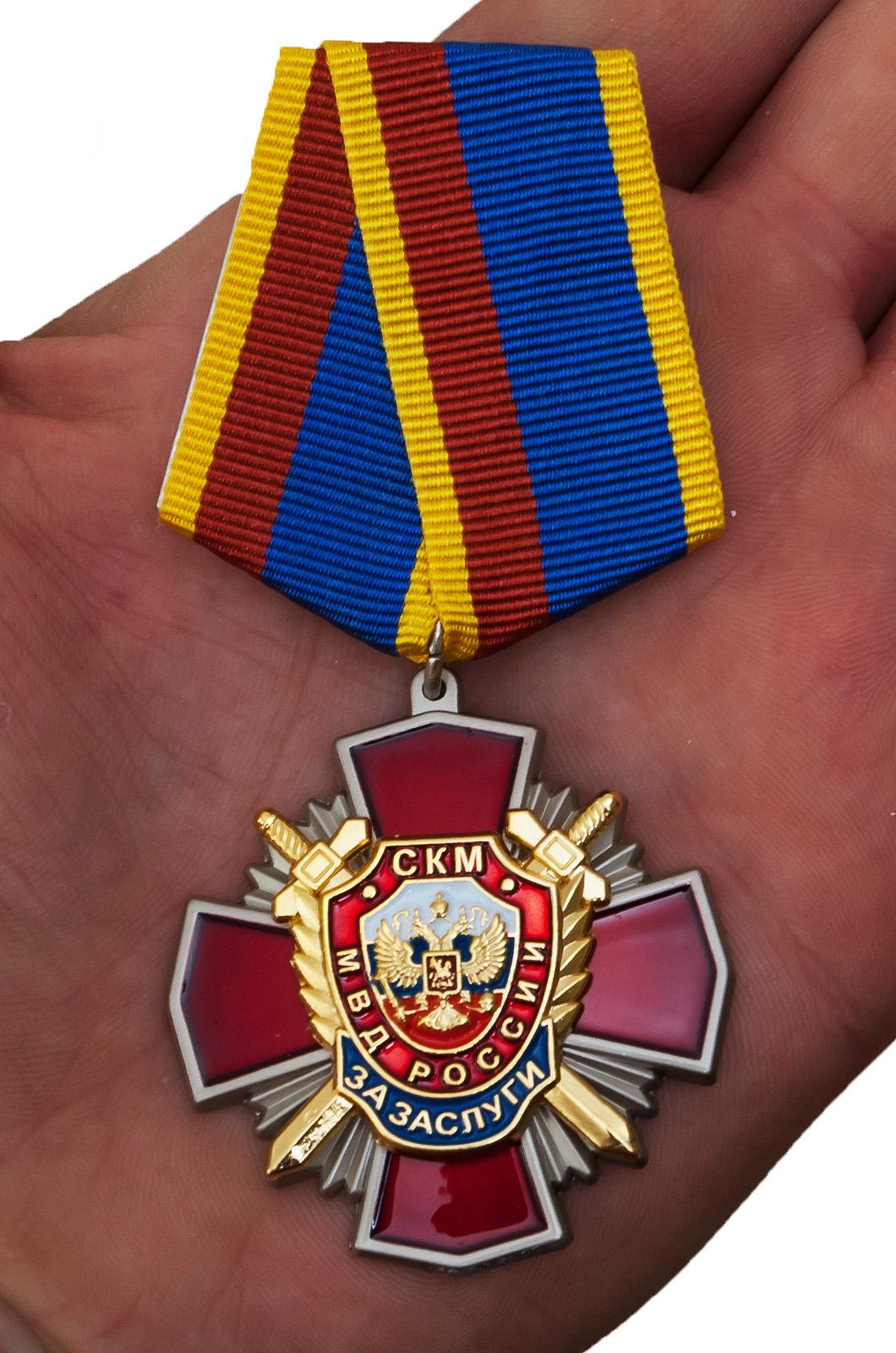 """Медаль Уголовного розыска """"За заслуги"""" в бордовом футляре из флока с прозрачной крышкой - вид на ладони"""