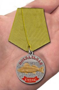 """Медаль в подарок рыбаку """"Судак"""" в нарядном футляре из флока бордового цвета - вид на ладони"""