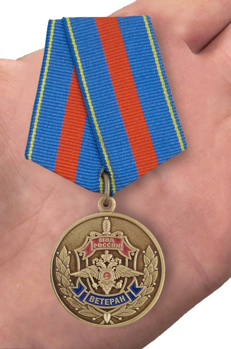"""Медаль Ветеран МВД """"Служим России, служим закону"""" в бархатистом футляре из флока - вид на ладони"""