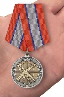 Медаль Ветерану боевых действий в нарядном футляре из бархатистого флока - вид на ладони