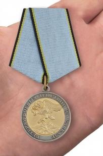 Медаль Ветерану боевых действий на Кавказе в наградном футляре из бордового флока - вид на ладони