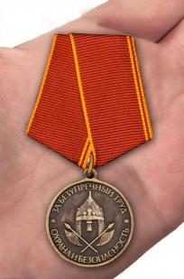 """Медаль """"За безупречный труд. Охрана и безопасность"""" в наградном футляре из бархатистого флока - вид на ладони"""