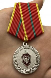 Медаль ФСБ РФ За отличие в военной службе I степени - вид на ладони