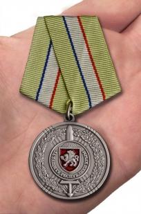 """Медаль """"За защиту Республики Крым"""" в футляре из бархатистого флока с пластиковой крышкой - вид на ладони"""