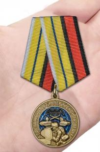 Нагрудная медаль За службу в артиллерийской разведке - вид на ладони