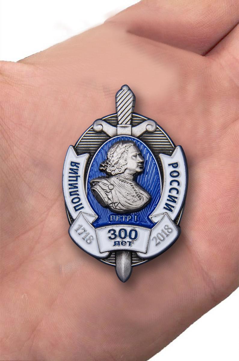 """Нагрудный знак """"300 лет полиции России"""" в бордовом футляре из флока - вид на ладони"""