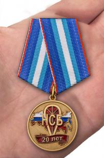 Памятная медаль 20 лет НСБ Негосударственная сфера безопасности - вид на ладони