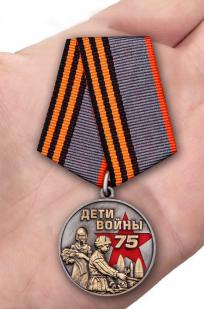 """Памятная медаль """"Дети войны"""" в футляре - вид на ладони"""