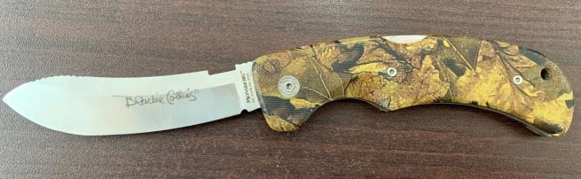 Складной нож с камуфлированной рукоятью и насечками на лезвии