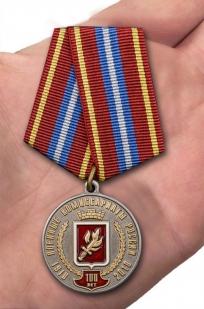 Юбилейная медаль За безупречную службу к 100-летию Военных комиссариатов России на подставке - вид на ладони