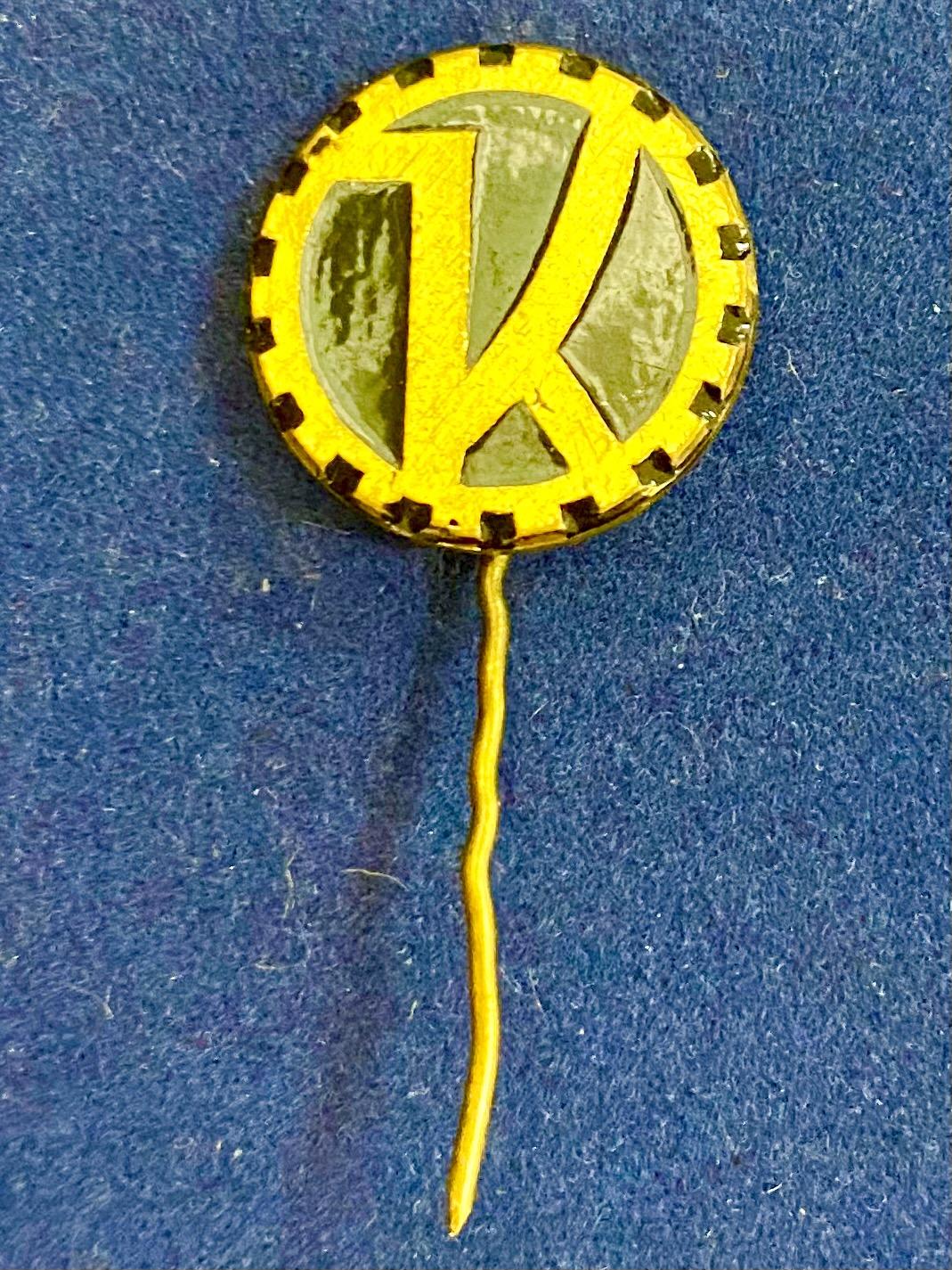 Значок на иголке с буквой К в шестеренке
