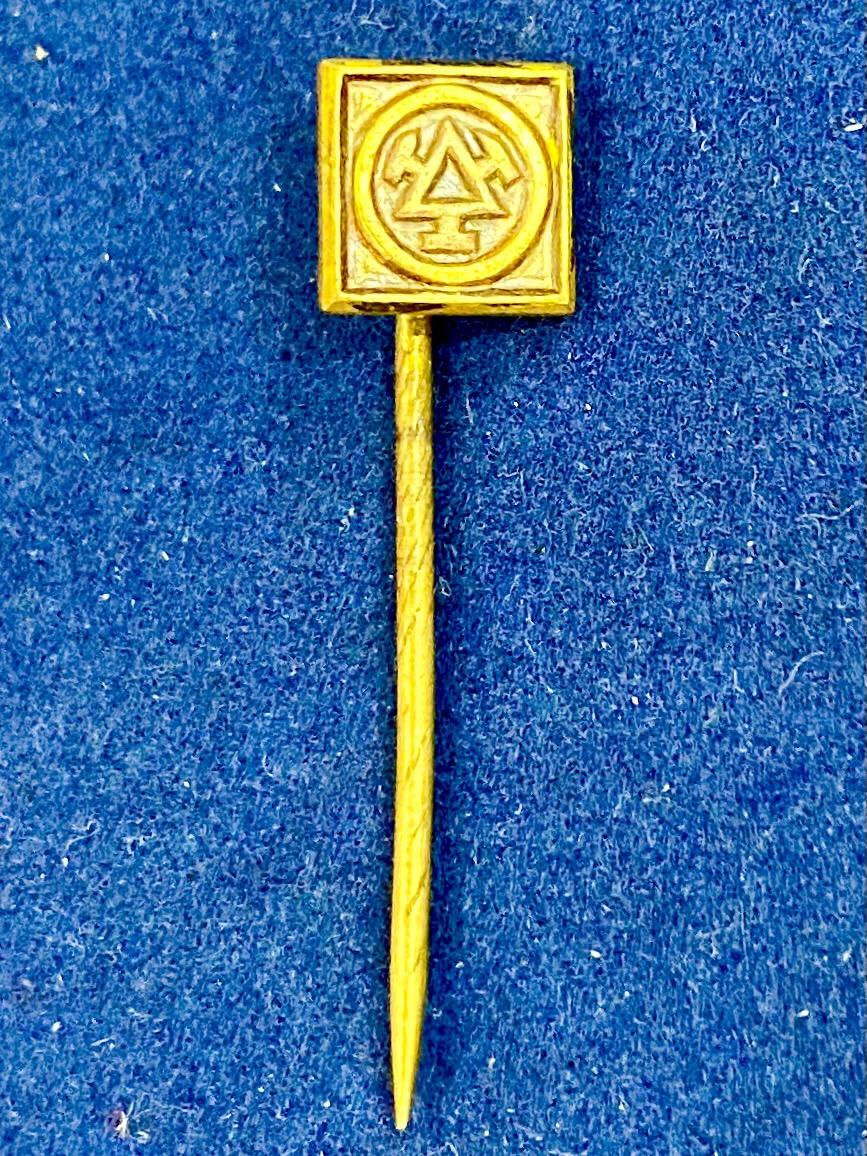 Значок на иголке с треугольником в круге
