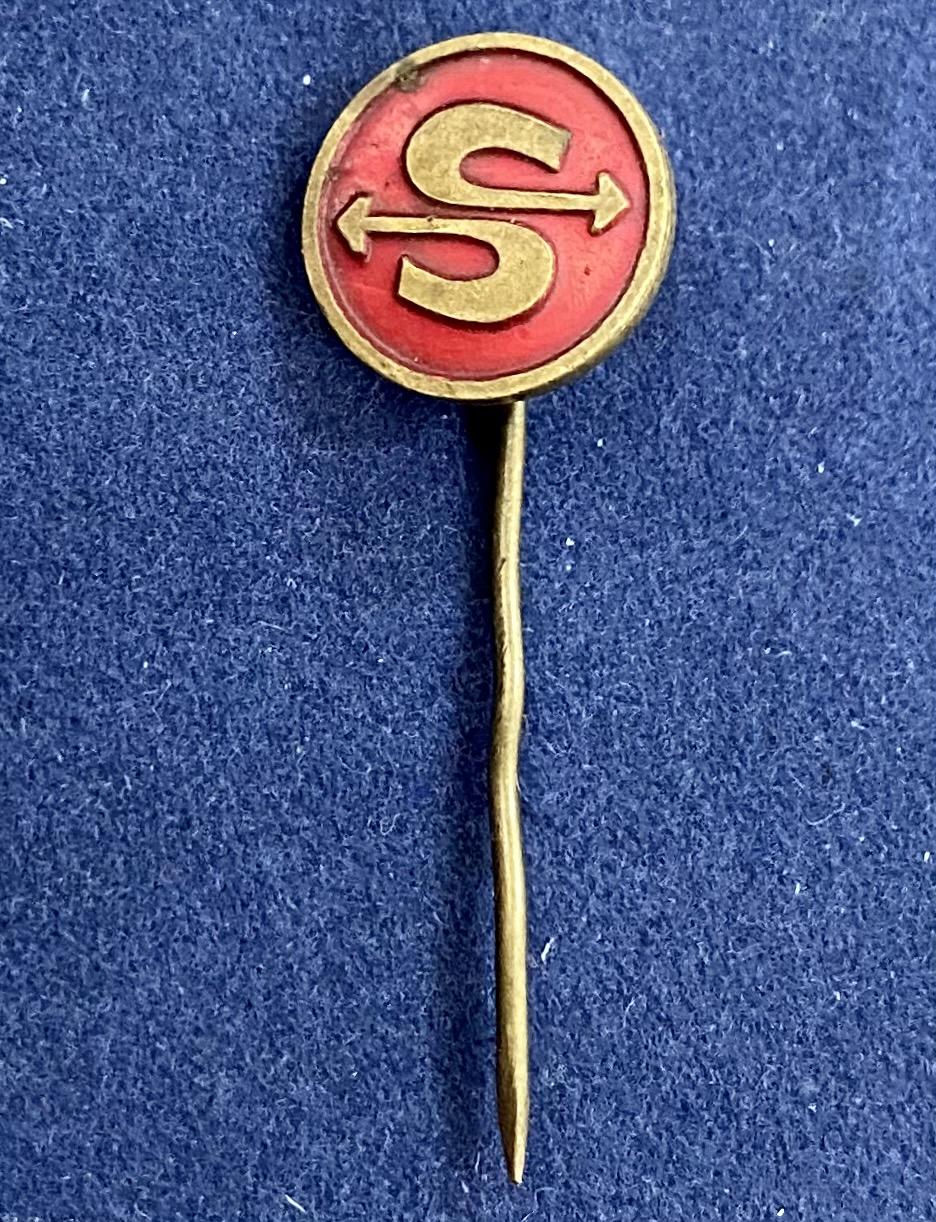 Значок на иголке со стилизованными стрелками