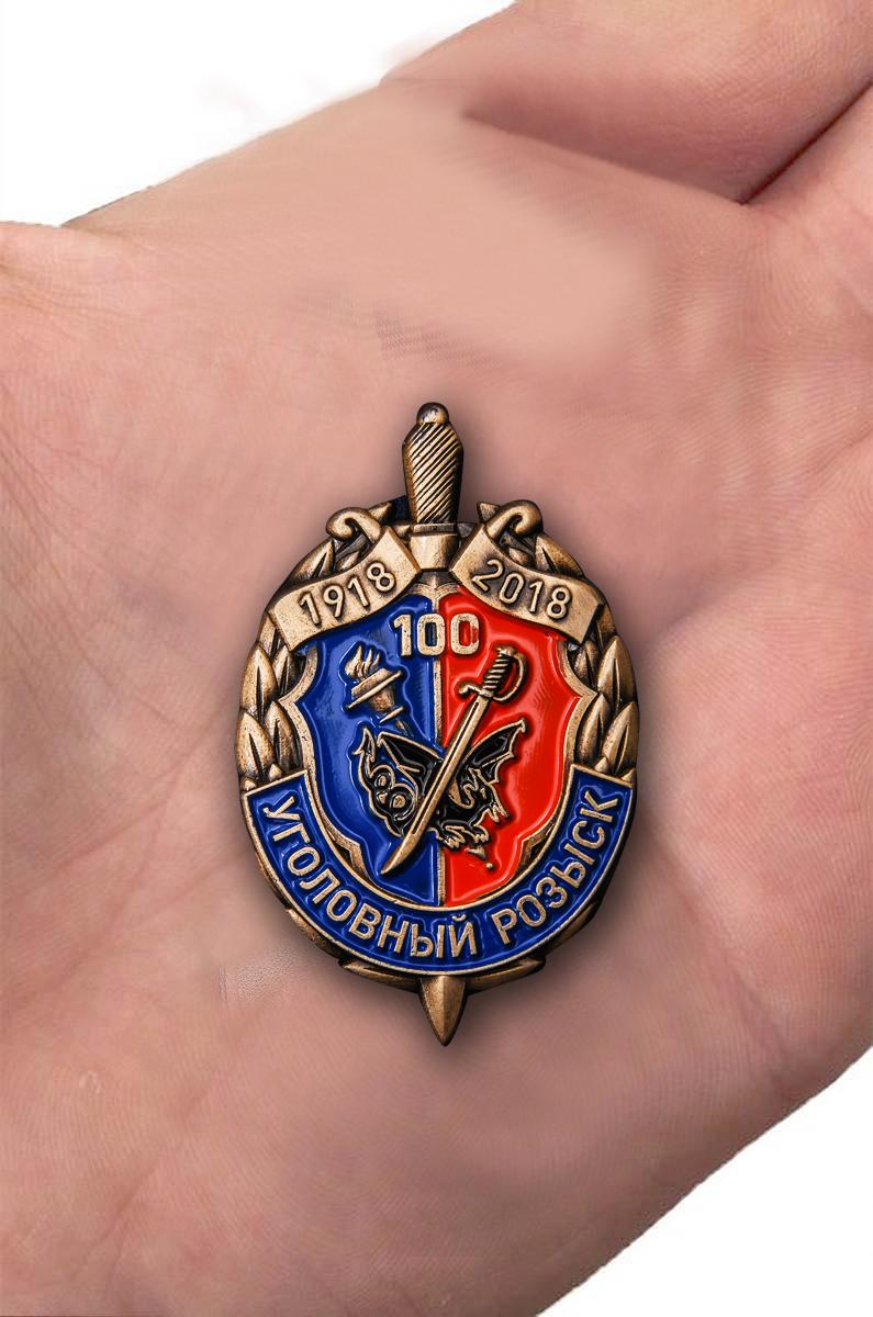 Знак к 100-летию Уголовного розыска в футляре из темно-бордового флока - вид на ладони