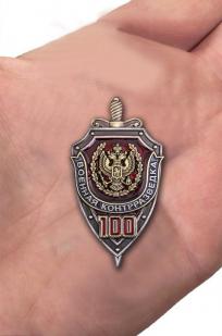 Знак к 100-летию Военной контрразведки в презентабельном футляре бордового цвета - вид на ладони